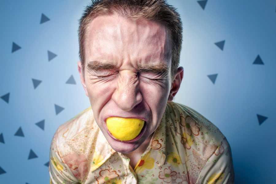 мужчина с лимоном во рту