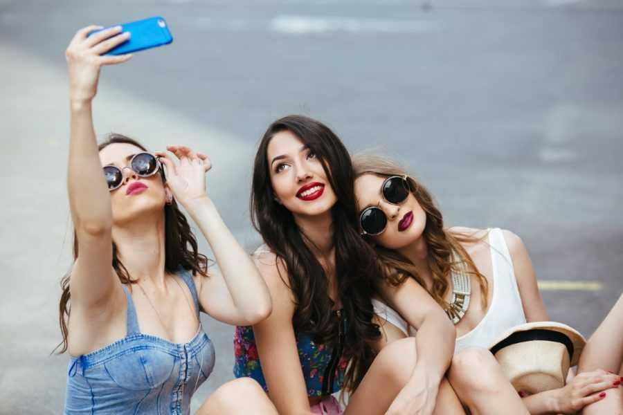 три девушки делают селфи