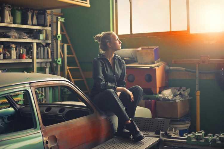 усталая девушка сидит в гараже
